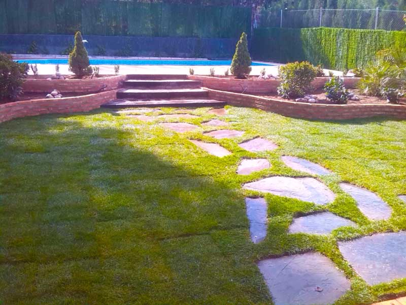Jardín rehabilitado con invasión de grama y sustituido por césped artificial con cama de arena y recibo de arena calibrada por encima.